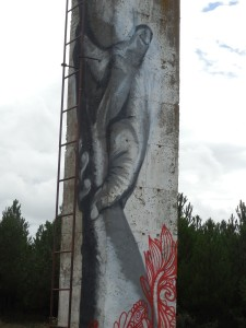 A gifted artist plies his trade on a cement pillar.