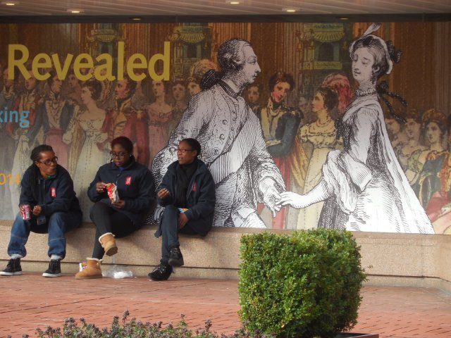 Three young men rest in front of the British Library, currently hosting an 18th century exhibit on Georgian England.