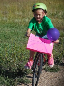 A young walker careens down the trail on her bike.